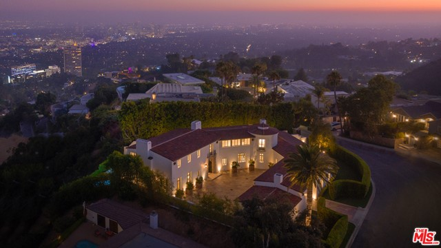 """Newly built and never occupied, this uniquely realized world class estate is on a quiet cul-de-sac in one of Los Angeles' most coveted neighborhoods with neighboring homes selling upwards of $40 million. Designed by award-winning architect Richardson Robertson III, renowned for """"Fleur de Lys"""" in Bel Air, the home boasts striking views from downtown to the ocean, with meticulously designed interiors and finished with the finest European materials. Features include four bedrooms, eight baths, 800-bottle wine cellar, theater, library and a  sparkling pool with skyline city views. The lavish master suite features fireplaces in the bedroom and sitting room capturing sparkling, top-of-the-world views. Unique to the area, a Porte cochere leads to lush, level gardens circling the grounds. A perfect combination of International luxury and glamorous Hollywood lifestyle."""