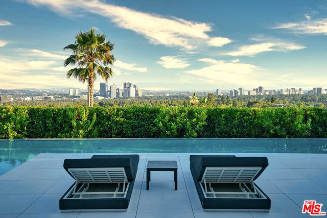 This newly-constructed home in the heart of Beverly Hills is a triumph of style and design, showcasing 270 degree views from Downtown to the ocean. Located at the end of a cul-de-sac and walled in by mature trees, this estate offers privacy and tranquility. Renowned designer Joseph Ferrugio created a dynamic palate, from beechwood ceilings and walls wrapped in walnut to a backlit onyx bar, amethyst slab powder room, and elevator encased in a phenomenal resin chamber. Automated Fleetwood pocket doors capture far-reaching views and create a seamless indoor-outdoor flow to an expansive terrace with a distinctive 110 ft infinity pool and fire features. Floating stairs lead to the top level with a wraparound terrace, 2 guest suites, a spacious master suite with a sitting area, fireplace, showroom closet and gorgeous bathroom. A lower entertainers level holds a walk-in wine cellar, theater, wellness center, auto gallery, marble bar with a window to the swimming pool, and living green wall.