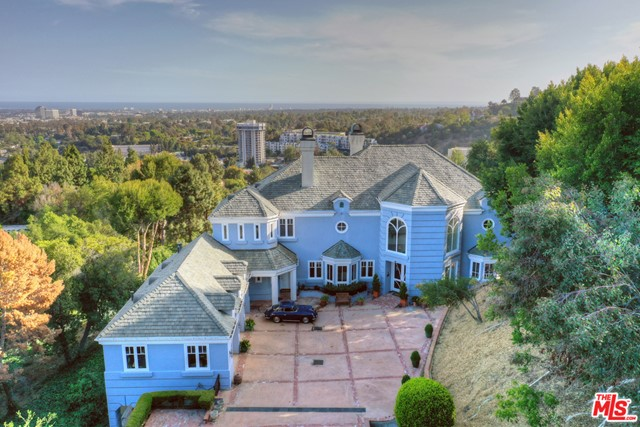 This gated, grand French view estate remodeled in 1991 with long driveway was designed by Richard Landry located in lower Bel Air and is set on 1.2 acres. It offers soaring ceilings, jetliner views of the city, ocean, Palos Verdes and Catalina, incredible scale, privacy and architectural integrity. From the moment you step inside this romantic home you know it was designed for those that entertain with an excellent floor plan, sparkling pool, wine cellar, full bar with refrigerator, 2 story library, 2 sided wood-burning fireplace, and numerous living spaces overlooking the city. The gourmet kitchen features custom cabinets done  by the renowned Vern Hartvigso, custom  appliances featuring three ovens, two warmers, a built-in 53K BTU Wok with exhaust hood, a Range with 4 gas burners and 2 haligen electric tops. The two master suites offer incredible views with phenomenal closet space/storage. This home is impeccable, timeless and offers complete privacy with an ultra prime location/ scale like no other. Tennis court foundation. Landry Design website.