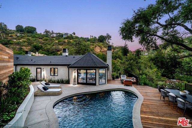 Immerse yourself in the apex of design and luxury in this to-the-studs renovation located in prime lower Bel Air. This modern villa checks every box. Unique to Stone Canyon this sophisticated home is saturated with natural light throughout. Designer Jess Cheng has created a perfect blend of wide plank oak flooring, marble countertops, wine cellar, soaring vaulted ceilings with exposed beams, designer fixtures, and a multitude of panoramic picture windows framing lush foliage and mountain views. The primary suite is built for pure serenity and features vaulted ceilings, walk-in closet, dual vanity, freestanding soaking tub, walk-in rain shower, and attached patio ideal for morning meditation. Enjoy lavish sunset evenings outside on the hundred year old oak studded terraced grounds with resort-inspired pool, private Jacuzzi, and cascading waterfall. Moments from the Hotel Bel-Air and surrounded by $20M+ homes, this one-of-a-kind estate represents the pinnacle of L.A. luxury living.