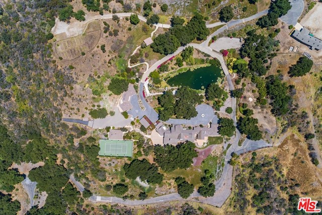 This is a remarkable, one-of-a-kind property consisting of 48 sprawling acres. Enter through a magnificent, custom gate and then up a quarter mile long, tree lined driveway to an unbelievably beautiful and secluded setting. There are currently  5 structures on site: a 12,000 s.f. main house (square footage approximate), tennis court with pavilion, separate guest houses, caretaker's unit, art gallery and studio and plenty of room for horses. In the center of this amazing property is the most serene and tranquil lake with waterfalls all surrounded by lush landscaping and expansive grounds. The property has its own well.  This property is ready for the right buyer to create their own compound with infrastructure already in place.