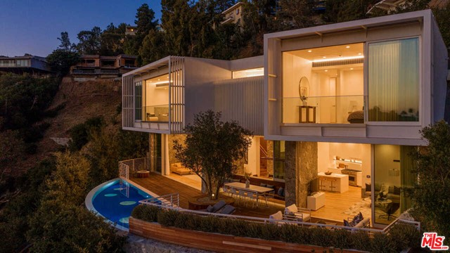 Situated on a private promontory, this contemporary new architectural is nestled into the hillside capturing sweeping canyon, city & ocean views. Envisioned by architect Ivan Ivanov, the approx. 9,312-sq-ft home boasts hand-laid stone walls, 12 ceilings, oak floors from reclaimed 19th-century barn & modern chefs kitchen with Thermador appliances. Floor-to-ceiling glass walls connect indoor-outdoor living, opening to the infinity-edged pool with windows to the gym below. Expansive terraces boast a built-in BBQ and olive tree, among the 50 new trees planted onsite. 5 bedroom suites include 2 upper-level masters, both with a spacious soaking tub. The lower entertainers level features a stunning bar, 3,000-bottle wine cellar, gym & theater. Features include a Zen-inspired backyard with redwood hot tub & yoga deck, Carrera marble baths, elevator, KNX smart system & 2-car garage. This spectacular, private contemporary retreat is located moments from downtown Beverly Hills.