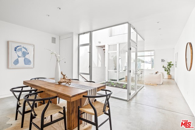 This architectural gem perfectly embodies California urban living, set above famed Abbot Kinney Blvd in a beautifully designed mixed-use building by Michael Sant. Blending a simple, understated elegance with a more modern aesthetic, this unit boasts an open layout, polished concrete floors, floating stairs, and warm wood details. Floor-to-ceiling glass windows and walls create a continuous connection to the private outdoor areas, and flood the unit with natural light. A courtyard off the kitchen provides the perfect setting for outdoor dining, and separates the kitchen and main living spaces from a detached guest bedroom with en-suite bathroom. Upstairs, the master suite opens to a spacious terrace with fireplace, and a separate bonus room offers the flexibility for an office/studio or third bedroom. Located amongst some of LAs best shops and restaurants, and just minutes to the beach!