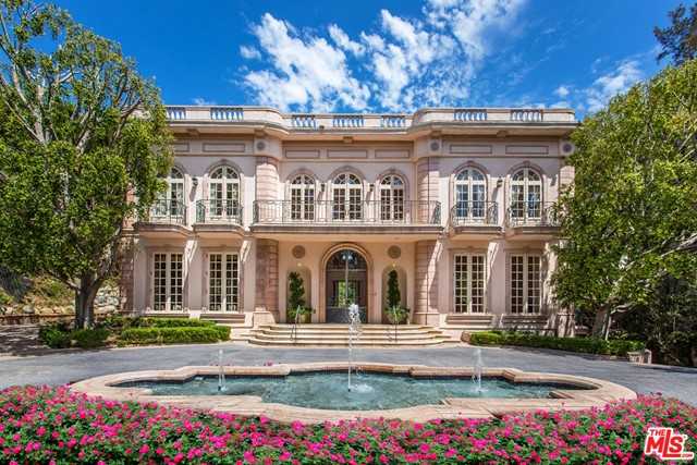 """Located on Mapleton Drive,  Holmby Hill's most prestigious street, this elegant, gated estate known as the """"Le Chateau Rose"""" was built by one of Architectural Digest founders emulating Marie Antoinette's famous summer palace at Versailles, the Petit Trianon. Past the dramatic reflective pool with triple fountains set in the center of the large circular cobblestone motor court, one enters this magnificent residence through 14' glass and verdigris wrought iron doors, greeted by daylight from a 46' high dome two stories overhead. Suspended from the center of the dome is a stunning massive 18thc. Baccarat crystal chandelier surrounded by the dramatic marble circular double stairway. Off this majestic entry, one encounters vast public rooms all with marble fireplaces, French doors and 14 high ceilings:  the cherrywood paneled library, the Parisian living room surrounded by waterfalls, the formal marbled dining room, the limestone and wood family room and two marble powder rooms. The 1800sq ft. master bedroom suite contains 3 fireplaces, a sitting room, several balconies, wet bar, and a marble spa. There are three separate guest suites with private baths, self-contained staff quarters, wine cellar, an elevator servicing all 3 floors, pool, tennis court and fountains."""