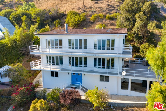 The epitome of West Coast living is here at this stunning four-bedroom, three-bathroom home on Castlewood Drive in Malibu. Located just minutes off the Pacific Coast Highway, one can take in the sea air on one of Malibu's infamous beaches. Boasting the best of both worlds, it is far enough into the canyon to provide endless mountain and ocean views, peace and extreme privacy. Work from home, read or watch the sunsets from one of two wraparound decks. This tri level home is filled with natural light throughout, has recently updated bathrooms and plenty of living and dining space. A huge pole barn on this whopping 1.6 acre lot makes the potential here endless. Truly a unique opportunity in one of Los Angeles' most desirable neighborhoods.