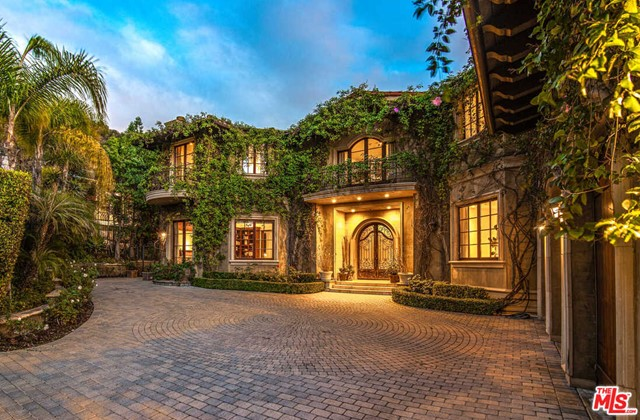 This private Tuscan villa is tucked away at the end of a cul-de-sac, minutes from Rodeo Drive. It stretches across lush grounds & blends a classical style w/contemporary amenities. Upon entry, one is greeted with a stunning 2-story formal entry w/winding grand staircase & Chihuly blown glass chandelier hanging above. This home features 5 bed, 7 bath, an office, media room, 2 bars & entertainment loft. Interior details including walnut hardwood floors throughout, vaulted ceilings, exposed beams, imported French doors &windows. Formal living &dining rooms merge seamlessly into the massive gourmet kitchen w/Viking appliances, large island, & walk-in pantry. Surrounded by trees & hills, every room offers stunning views overlooking gardens. Private &Ideal for outdoor entertaining with a heated pool, BBQ, fire pit, dining area &endless garden views. Master suite includes his/her bath, spacious closets, fireplace, private terrace &charming sitting room. A tremendous value in a prime location.