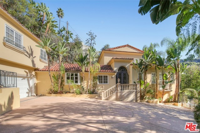 A short drive from the Beverly Hills Hotel leads to the gates of this serene and  sunny villa. Take a few steps up to the entry porch, push open the wrought-iron doors, and find yourself in a stately foyer. To the right is the large, high-ceilinged living room with luminous windows, Italianate fireplace, and hardwood floors. To the left lies the well-proportioned formal dining room w/ French doors opening to an intimate dining terrace & fountain. Beyond lies the chef's kitchen with a banquette, large pantry, and double Subzero. 2 ensuite bedrooms, a study, and a powder room complete the main level. The master suite occupies the entire upper floor w/ 2 balconies, 2 bathrooms, 2 walk-in closets. The lower level consists of a guest bedroom, 2 baths, bar/entertainment room which flows out to the salt-water infinity pool & spa. Massive ficus trees surround the grounds making them private and quiet. Separate guest house with 2 bedrooms and 2 baths. Two car garage and 5 car gated motor court.
