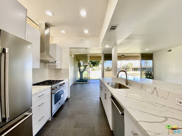 UPDATED MID-CENTURY GEM! Richard Harrison designed 2BR/2BA home with lake view on 16th fairway has been professionally remodeled for today's aesthetics. Enclosed courtyard den removed and returned back to a large, private, sunny courtyard patio w/western St. Jacinto mountain views. (Unit now approx. 1,545 SF--Buyer to verify.) Tall ceilings, open kitchen w/stainless steel appliances; Bertazzoni 5-burner gas range w/hood & white Cambria quartz countertops. Bathroom skylights, white 3-D porcelain tile shower stalls w/new glass shower doors, undermounted sinks, Grohe single-lever faucets, Kohler WC. Terrazzo-like tile flooring throughout extends to terrace lanai. LED recessed lights, clerestory windows, lever door handles. Single carport nearby with parking directly in front. 7 Lakes Country Club is a 24/7 guard gated golf community: executive 18-hole golf course (par 58), 15 pools/15 spas, William Cody clubhouse w/dining, golf/pro shop, electric car charging stations.