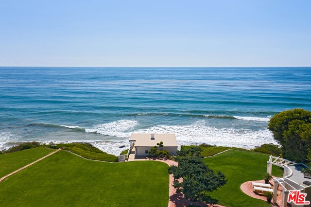 Views! Views! Views! This dramatic Cliff May-designed oceanfront compound w/2-GHs on apx. 1.9+ acres & 131ft of beach frontage sit behind gates among manicured gardens & a meandering waterway w/bridges & waterfalls. The 4 bed, 5 bath main house w/2-car garage & ocean views from nearly every room, offers beamed ceilings, stone floors, & wide French doors that open onto vast lawns, mature trees & panoramic ocean views. The ocean-view living/sitting/dining great room w/FP & massive beams opens to brick portico for outdoor entertaining. The well-equipped kitchen has an apx. 4.3'x4.3' interior refrigerator, large 2-tier island, breakfast bar w/doors to outdoor dining area. A huge entertainment space has wet bar & French doors to outdoor patio/garden. The upstairs rooms w/beamed cathedral ceilings include an apx. 1300s.f. owners suite w/whole-tree mantel FP, French doors to full-width ocean-view balcony, a luxe bath w/sunken tub, custom closets & reading nook, and includes an ocean-view office w/hardwood floors, built-ins & balcony. GH #1 is perfect for whale watching w/deck includes a kitchenette & steps to beach. GH #2 has a 2-story ceiling, kitchenette, spiral staircase to a sleeping loft & a 3/4 bath. Add'l structures include a sauna/bathhouse w/hot tub, & a red barn used for storage or 2-car garage. There is an add'l 4-car garage & ample guest parking.