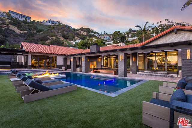 """The most exquisitely conceived single-story estate with city/ocean/canyon views on one of the most sought after streets in the Hills. The owner spent more than $4M to remodel the home for himself, crafting a timeless masterpiece with soaring wood-lined vaulted ceilings, a master bedroom that turns into a movie theater, private library with a working bell-tower clock, master bath with 15 ft. dual-shower and unlacquered brass fixtures, custom sauna, copper outdoor tub, countertops and vanities made from solid steel, custom built and suede-lined walk-in closets, a hidden 85"""" living room TV that comes up from a concrete bunker under the house, floating stairs to a wine cellar, copper/steel custom bar with recessed steel and leather niches, four fireplaces, outdoor BBQ/bar, LED lighting and smart home technology throughout. An unrivaled chef's kitchen replete with Gaggenau appliances, Leicht imported German cabinetry, and Mavam coffee maker. Lighting throughout from Buster + Punch, London."""