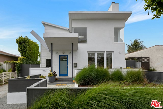 Fresh, contemporary Architectural home on a tree-lined street close to everything Santa Monica has to offer. The double butterfly roof sets this home apart and invites you through the front yard to the large porch. Designed with great attention to detail, this home features 14 clerestory windows illuminating the interior with natural light, wood floors adding warmth, built-in custom cabinetry, and an open floor plan that flows from living to dining to the kitchen. French doors open from the front porch to the living room with two-story ceilings and fireplace. The kitchen has a breakfast bar, tons of storage, and high-end appliances. The main floor includes the primary suite with a spa-like ensuite bathroom in a relaxing blue hue and it opens to the rear yard offering fruit trees and a detached garage. The good-sized second ensuite bedroom is also on the main floor. Upstairs youll find the third ensuite bedroom, a large airy loft family room, laundry room, office space, and a spacious deck with gas BBQ hookup and mountain views. This happy and bright home is in a great neighborhood with easy access to the beach, local restaurants, Gelsons, Whole Foods, coffee shops and all of the Santa Monica local favorites!