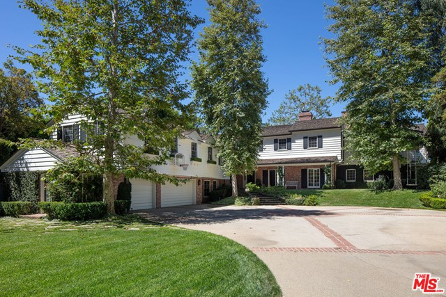 """Enter through tall private gates past a huge front lawn to this sprawling remodeled 1930's East Coast Traditional estate sited on a nearly all flat 28,000 Sq Ft """"rim"""" lot with dramatic views in a desirable north of Sunset Brentwood locale.  Living room with tall French doors and fireplace, warm paneled library/den & beautiful formal dining room with views, a real cook's kitchen with family dining, adjacent family room with fireplace and French doors. Three family bedroom suites complete the downstairs.  The 2nd floor offers a sumptuous owner's suite with fireplace and French doors to the view, two elegant bathrooms and dual offices/gym. Two additional bedroom suites share the upstairs with a huge family/media room. Enormous front yard and lovely rear garden with pool, spa, outdoor fireplace overlooking canyon and ocean views. Located in close proximity to shopping and the city's top schools. This extraordinary home has it all."""