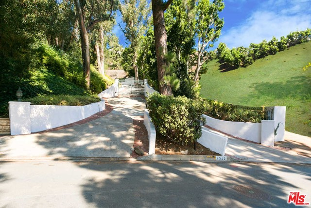 Two huge separate lots with views in Beverly Hills proper! These properties are gated up a long majestic driveway, which opens up onto the two huge legal lots with views. Nestled on one lot is a charming 5,950 square foot house with a swimming pool. The other lot has a huge flat pad with canyon and city light views. This is a great find for a developer to build two spec houses or a fantastic opportunity for an owner-user to build a fabulous private compound in Beverly Hills proper, directly across the street from a $30 million estate.