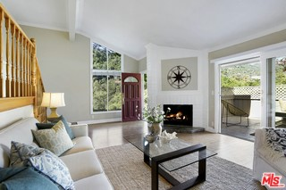 Wouldn't it be nice to live within minutes of what the city offers & be surrounded by tranquility & natural beauty? Now you can! This corner unit in the Palisades Highlands sits on the rim of a canyon with 180° views of the Santa Monica Mountain Range. The living room has a fireplace & opens to a private patio. The dining room is adjacent to a bright kitchen; & the downstairs bedroom, currently used as an office/den, is adjacent to a bathroom with a shower. On the second floor, the large Master suite has vaulted ceilings, a master bathroom, & a walk-in closet. The second upstairs bedroom has an en-suite bathroom. Another advantage of living here is the hiking trails & membership to the exclusive Santa Ynez Rec Center with its putting green, tennis courts, Olympic size pool, hot tub, children's pool, gym & clubhouse equipped with a full kitchen for catered events. Start your day looking out at the green canyons with the sounds of the gurgling fountain just 20 steps from your front door.