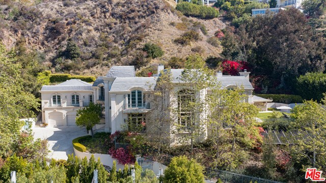 This grand Contemporary Mediterranean estate is located up a private drive at the end of a secluded cul-de-sac. Enter through gates to an impressive motor court with parking for up to 15 cars and a 5 car garage. The home features large rooms and high ceilings, tall impressive iron and glass entry doors, a two-story entry, marble floors, an elevator, double powder rooms, and a second-floor family area. The 11,251 sq. ft. of interior features 7 bedrooms, 9 baths, a gourmet kitchen with a double island with granite counters, breakfast room with French doors. Spacious family room featuring hardwood floors, wet bar, fireplace, and French doors that lead to a grass lawn and pool with spa and cabana, secondary yard provides room for a sports court and/or children's play area. The formal library includes a loft. Spacious master bedroom with fireplace, separate his and her baths, large walk-in closets, large private balcony with views of the pool.
