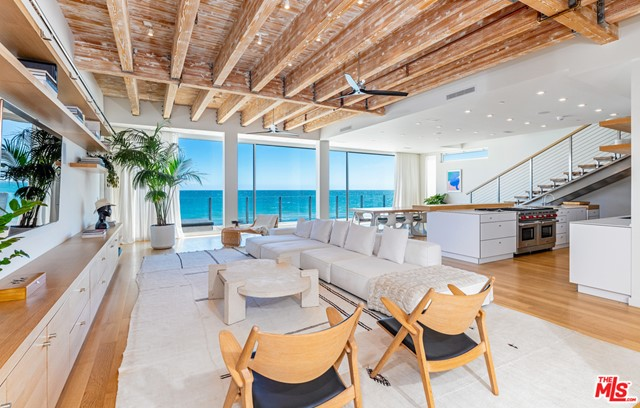 An architectural triumph, 25160 Malibu Road showcases masterful craftsmanship and spectacular waterfront living. Envisioned by Scott Gillen of UnvarnishedCo., the home features a dramatic great room with 12-foot exposed beam ceilings, hand-scraped oak floors and grand Fleetwood sliding glass doors that open to the shoreline. Wood accents combine with the fresh white color scheme. The custom gourmet kitchen offers European Caesarstone counters and Wolf appliances. A floating stainless steel staircase leads to a second spacious media/living room. In the ultra-luxurious primary suite, walls of glass open to a private deck and dramatic sunset and Point Dume views and a large walk-in closet includes built-in wood cabinetry. Two additional spacious suites are located upstairs. Downstairs, a fourth bedroom can be used as an office or gym. With a two-car garage and proximity to fine dining and shopping, experience a Malibu lifestyle that is nothing short of extraordinary.