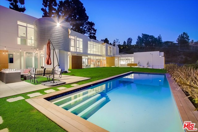 Seldom does an architectural triumph like this come to market. Designed and built for himself by acclaimed architect Larry Schlossberg AIA. On a serene cul de sac with a prestigious Beverly Hills, 90210 address.  Floor to ceiling walls of glass, polished cement floors and sky high ceilings to 21 feet. In addition, blank canvas walls for the accomplished art collector.  Large open floor-plan with massive  gourmet kitchen and professional, stainless steal appliances.  Primary Suite with  glorious views overlooking the expansive backyard and beyond. Stunning exterior with maintenance free Proderma wood cladding and aluminum shingles. Gym, study, maids, massage room and more.  The beautiful, entertainment pool house, is perfectly sited next to the expansive, heated swimming pool. All this and more, with  a moments drive to the incredible shopping of Rodeo Drive and all that Beverly Hills has to offer.