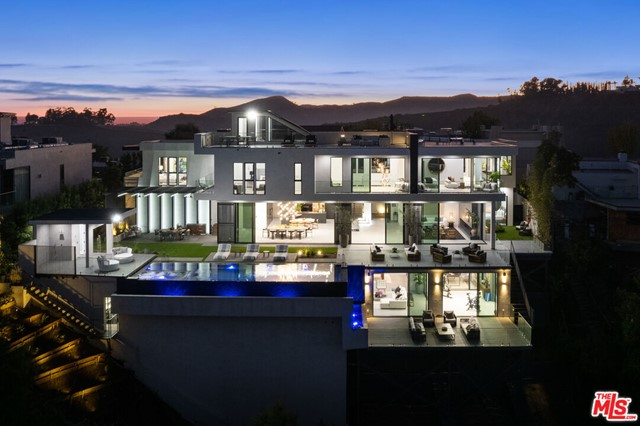 Conveniently located in the heart of Bel-Air with mesmerizing views overlooking the Stone Canyon Reservoir and rolling mountains, this modern marvel will leave anyone speechless. No expense was spared obtaining the finest materials to create this architectural triumph. The ground levels open floor plan presents an effortless indoor outdoor flow showcasing a modern chef's kitchen with professional grade appliances, formal dining, and living room all lined with disappearing walls of glass that provide an abundance of natural light. The backyard features an outdoor kitchen, dining al fresco, and an expansive infinity edge pool and spa that compliment the breathtaking scenery. The lower level is an entertainers paradise boasting a spacious home theater, wine cellar, game room, gym, and separate terrace. In addition to the 5 comfortable ensuite bedrooms, the outstanding master bedroom is accompanied by a luxurious bath with dual vanities and a soaking tub, designer walk-in closet, and a private balcony.  Completing the seemingly endless places to entertain is a vast rooftop deck that allows one to fully appreciate the paramount city and mountain views from sunrise to sunset.
