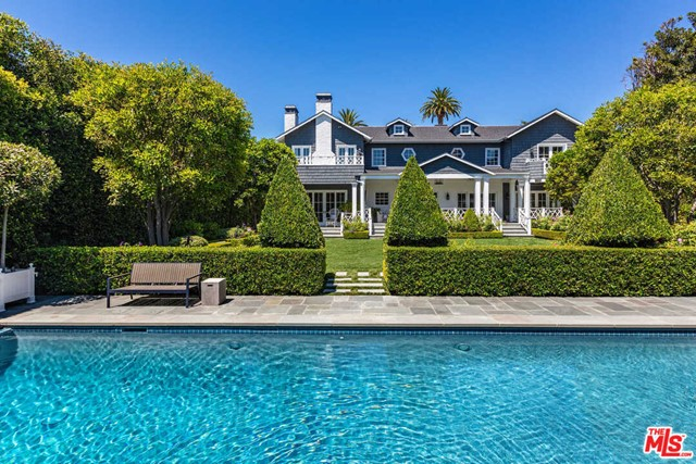 Situated in the historic Hancock Park/Windsor Square neighborhood, this iconic Nantucket-inspired estate offers approx. 8,058 sq ft of living space, surrounded by leafy hedges and exquisite landscaping. Recently reconstructed, the residence masterfully blends traditional architecture and crisp, modern design, with detailed craftsmanship including crown moldings, intricate paneling & marble floors. The 1st floor features formal living & dining rooms, a library, chefs kitchen & adjacent family room. 5 bedrooms include the exceptional primary with sitting room, spa-style bath and 2 walk-in dressing rooms. Additional rooms include a den, office, gym and 13-seat theater. French doors open to shaded terraces, expansive lawn and heated pool/spa. A detached guest house with kitchen and viewing terrace over the pool sits above the 2-car garage. While offering absolute privacy and serenity, the estate is located moments from Larchmont world-class dining, shopping and entertainment.