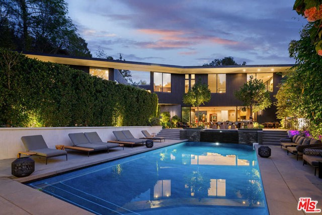 Bringing Aspen to LA. Welcome to a contemporary, zen-inspired architectural gem built by world-renowned architect interiors firm, Masastudio. Located on a quiet, gated cul-de-sac, the home is surrounded by trees, mature landscaping and sits on a lush acre in the Hollywood Hills. The peaceful main courtyard, surrounded by an expansive, multi-level living space. Skylights and soaring ceilings create sun-soaked rooms. The kitchen features stainless steel Miele appliances, stone countertops, floor-to-ceiling cabinetry, an island, and doors that open up to the pool pavilion. Find an outdoor kitchen, a waterfall, resort-style pool, pizza oven, and winding paths. The primary suite offers a large, glass-enclosed stone shower, surrounded by a walk-through closet. The 6 ensuite bedrooms present unique styles and details such stone accents and built-ins. A lower level includes a recording space, theater, bar, and gym. Enjoy the convenience of a 3-car garage and Hollywood shopping and restaurants.