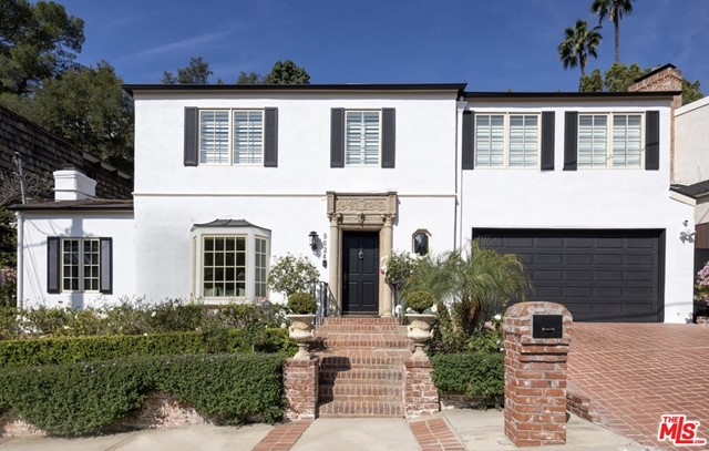 Just minutes from the world-renowned shopping and restaurants of Beverly Hills, yet privately nestled on a quiet street, this beautiful home is one of the best deals in Beverly Hills. Behind a gorgeous front door encompassed in custom stone lies an unbelievable floor plan accented with timeless charm. To the left is a spacious sunken family room and formal living room, each boasting custom crown moldings and marble fireplaces. Directly ahead awaits the inviting dining room and bright chefs kitchen with professional grade appliances. Through French doors from the dining or living rooms lies a haven of comfort and relaxation. The expansive backyard lush with mature landscaping is equipped with Sonos surround sound, a sparkling pool & spa, and an outdoor kitchen making it a wonderful setting to entertain friends and family. Meander up the authentic wooden staircase outfitted with sturdy cast-iron railings to the luxurious master bedroom with highlights including a fireplace, private balcony, marble bathroom, and two beguiling walk-in closets. This 3 bed 4 bath Beverly Hills home is a delightful oasis.