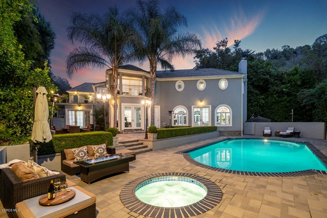This classic Beverly Crest estate, located just minutes north of Sunset Blvd in the renown upper flats of Beverly Hills, was completely rebuilt in 2011. Private and gated, this light-filled home features a sweeping marble staircase, reminiscent of the bygone Hollywood era and the estate's original owner, Errol Flynn. The home has a grand formal living room with French windows and doors, a large home office, a private lounge area with pocket French doors, and a spacious modern gourmet kitchen with newer high-end appliances, expansive crystal quartz center island, Sub Zero refrigerator, and a built-in Miele coffee station. The kitchen opens to a large family room, as well as the formal dining room. Adjacent to the kitchen is a maid's room with a full bathroom and laundry room. The upper level features a luxurious master bedroom suite with balcony, spacious his-and-hers dressing rooms with bathrooms, a separate steam shower, plus 3 large additional bedrooms (2 with ensuite baths and walk-in closets), and a 300 SF sundeck. The home's serene backyard features a salt-water pool & spa, built-in BBQ with sink and refrigerator, gas fire pit, retractable patio shade, outdoor heaters and sophisticated landscaping which lends complete privacy. Additional amenities include a separate workshop, gated driveway, 9-camera security system, backup power generator, 2 tankless water heaters, detached 2-car garage with built-in storage, upstairs bonus room and bathroom.