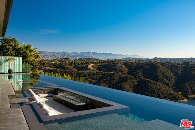 Once in a life time opportunity to seize this Bel Air mansion in the sky featuring close to 12,000 interior sqft w/ the best views Los Angeles has to offer, including 8 bedrooms and 11 baths. Impeccable materials handpicked from around the globe, combined with the luxurious finishes and disappearing glass walls showcasing lake, city and mountain views. Grand main floor w/ soaring ceilings, an Italian designed kitchen, dining, decks, outdoor seating, fire pit and a separate BBQ of the kitchen. Extravagant master suite with world views, a massive outdoor deck, and Tom Ford style closets, combined w/ a decadent bath including steam shower, soaker tub, and a fireplace. Amenities: Imposing entertainment space with a 3000 sqft garden, wine cellar, maids' room, 4 lvl elevator, gated driveway, 8 car garage, Sonos system, LED lights, crystal chandeliers, white oak floors. Estate affords endless living areas surrounded by views, w/70ft infinity pool w/spa,+ an enormous roof 2000 sqft roof deck.