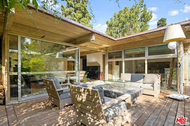 """William Wallace Reid, Architect,1953. This unassuming, private, sublime, sanctuary, is a South facing, jewel box. Placed on the brow of the canyon its floor-to-ceiling windows, and upper skylights, are strategically placed, capturing light and framing the borrowed space and views while coddled by mature trees and ocean breezes. The house is a work of art and a testament to details & style embracing the original post & beam design and vision of Architect William Wallace Reid and his wife Paula. The current owners stayed true to the original, complementing its soul with the comforts of the 21st century. Every part of the house has purpose without compromise of design. When entering the house one is immediately struck by the elevated materials and setting in nature. The house includes a luxurious main bedroom suite. When open to the living room the house is perfect for one or two individuals while also brilliant for entertaining the extended family and friends. The living room opens to the patio/gardens and canyon views with floor-to-ceiling windows and open beamed ceiling. The spacious family room and second bedroom/bath offer elevated comfort plus plenty of storage. The open cook's kitchen opens to another private outdoor kitchen/patio area enhanced by the pizza oven with the backdrop of a mature Eucalyptus tree. The house is situated on a street-to-street lot with the potential for adding a well thought out garage and ADU while still preserving the privacy of the existing house. The house is being sold fully furnished and outfitted.  You can see plans for the ADU under the """"Documents"""" tab."""