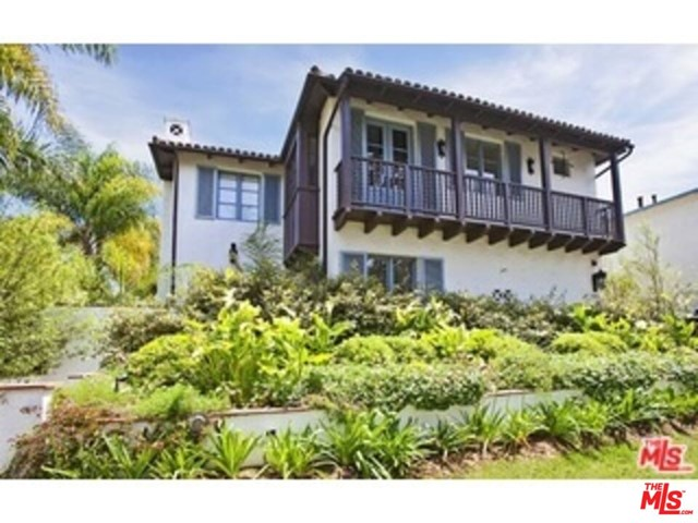 Stunning Spanish Colonial townhome designed by William Hefner. For those who appreciate the look and era of early Spanish masterpiece properties, look no further. Rarely do you find this level of quality workmanship, taste and attention to detail. Dark wood floors throughout and wood beam ceilings are complemented by vintage-style light fixtures. The open kitchen has Calcutta marble counters, farmhouse sink, Viking and Sub-Zero stainless appliances, accented with beautiful French nickel-finished faucets. High T & G wood ceilings highlight the master. Walker Zanger tiles and Waterworks fixtures complement the baths. Beautiful large wood windows and French doors open to the charming front and rear patios. Private garage with extra storage.